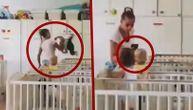 Snimak iz Zvečanske: Vaspitačica mlatara s bebom u ruci, pa fotografiše. Suspendovana je (VIDEO)