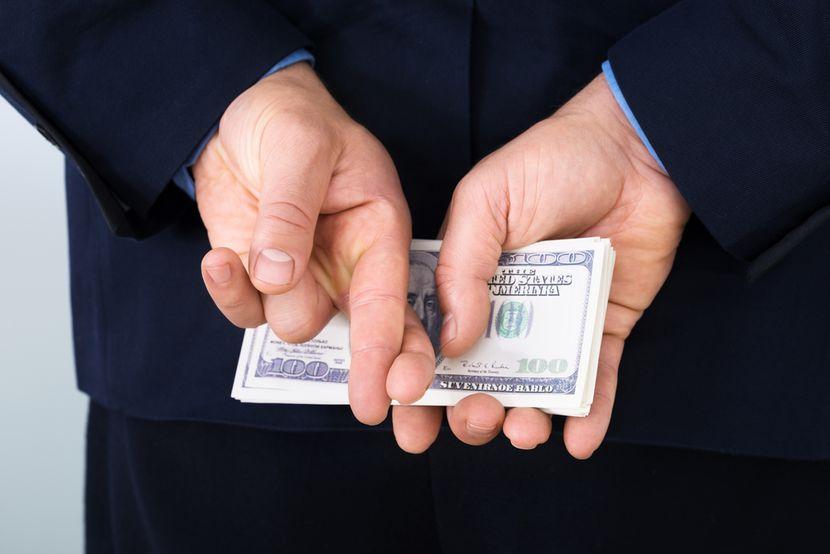 Biznismen drži novac, prekršteni prsti
